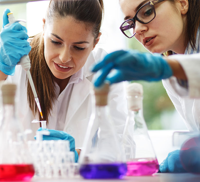 biotech lab scene of two women with one placing a solution into a test tube