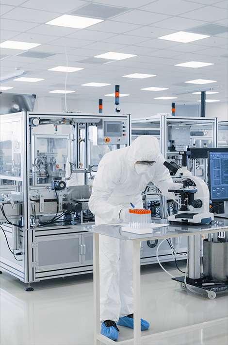 pharmaceutical clean room showing worker with microscope and test tube rack