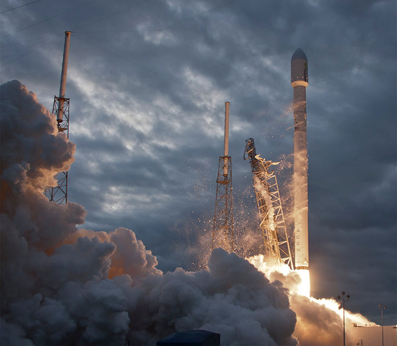 evening launch of spacex rocket at moment of liftoff