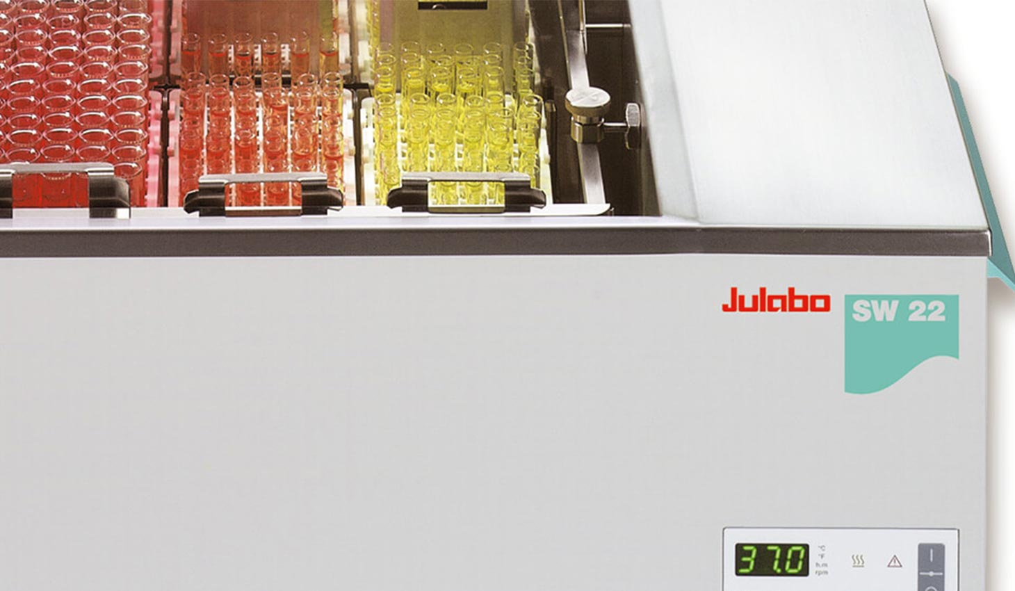 racks of test tubes filled with red and yellow liquid sitting in a Julabo SW22 temperature controller