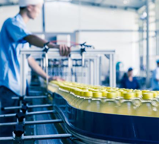 Beverage production line with filled bottles passing by on a conveyer