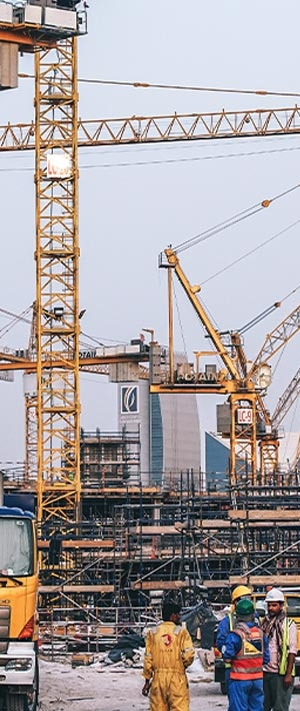 construction site with multiple cranes in the background and workers in hardhats in the foreground